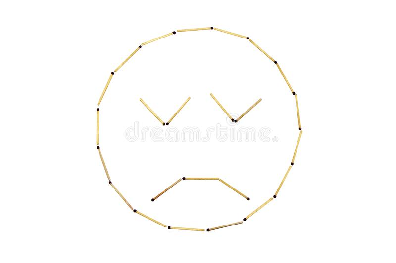 Smiley face Discontent is made out of matches. Human emotions. Discontent face. Matches in the form of a smiley are arranged against a white background. The stock photo