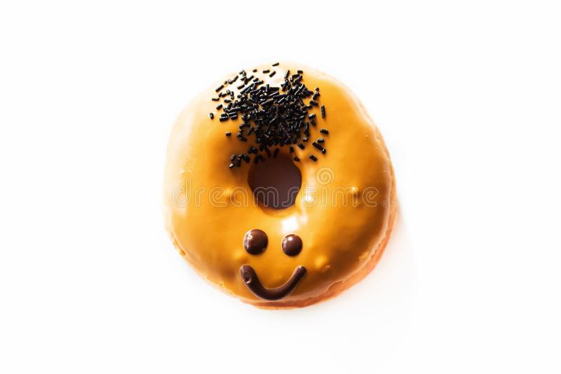 Smiley face donut. Caramel donut with a smiley face on it- emoji, emoticon stock photos