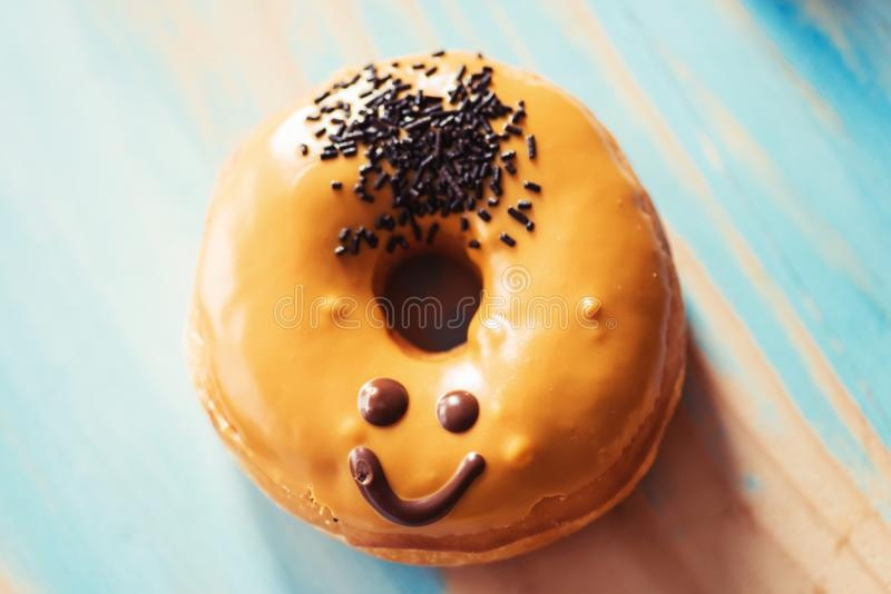 Smiley face donut. Caramel donut with a smiley face on it- emoji, emoticon stock photo