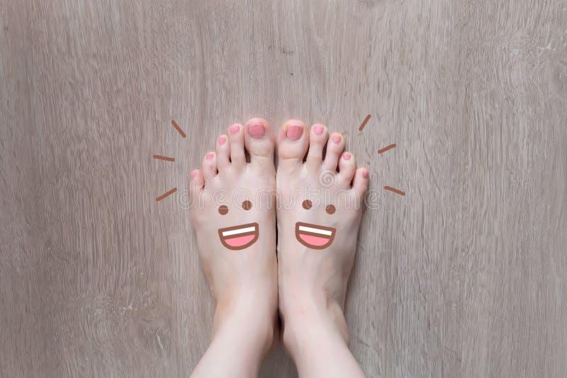 Smiley Face Drawn på tår Slut upp kvinnligt barfota på trägolvbakgrund royaltyfri foto