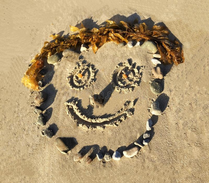 Smiley Face Drawn In The Sand royalty free stock photography