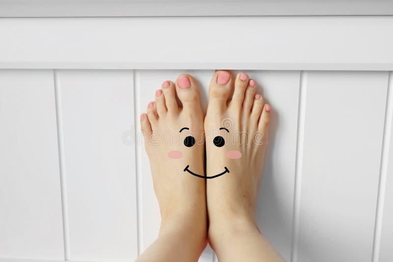 Smiley Face Emotion Barefoot Härlig kvinnlig fot på rosa tygsovrumbakgrund arkivfoto