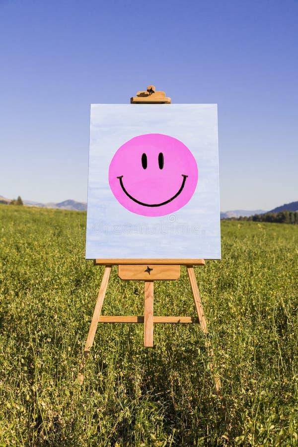 Smiley Face målning på staffli i grönt fält Lycka kreativitet, bra lynne, mental hälsabegrepp royaltyfri fotografi