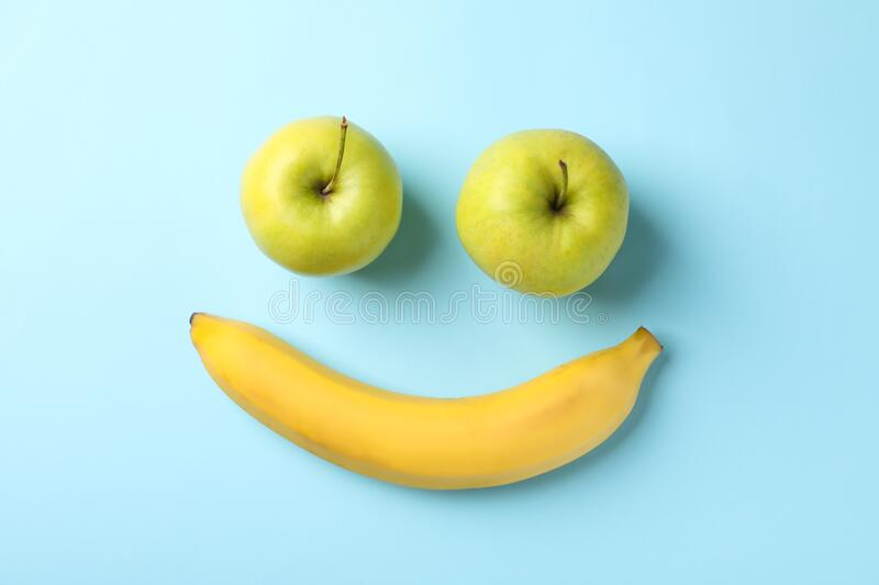 Smiley face made of bananas and apples on background. Smiley face made of bananas and apples on blue background royalty free stock photography