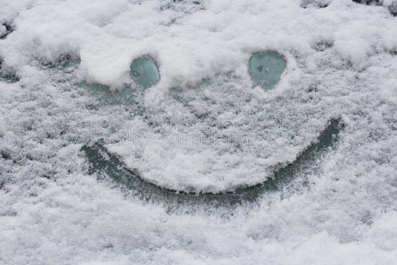 Smiley face on snow surface. Winter concept. royalty free stock photo