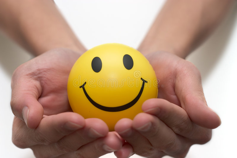 Smiley face in two hands. Smiley face ball in two hands stock photo