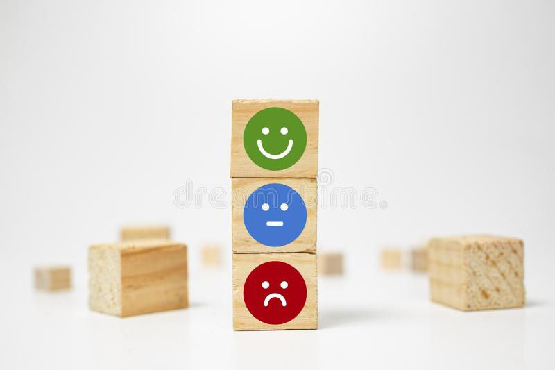 smiley face on wood block cube - business services rating customer experience, Satisfaction survey concept - Feedback royalty free stock image