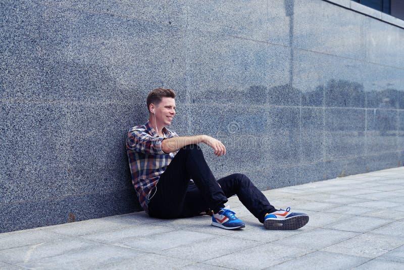 Smiley facet siedzi blisko ściany, słucha muzyka zdjęcie royalty free
