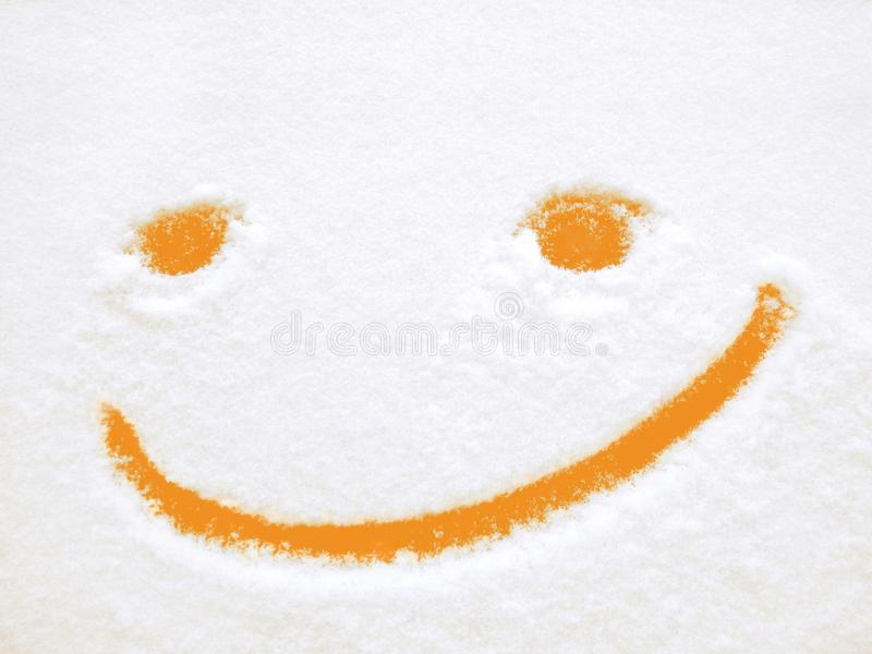 Smiley, funny orange emoticon, positive emotions, smile on snow. Funny orange emoticon on snow. Positive emotions in winter. Smile drawn on fresh snow royalty free stock photography