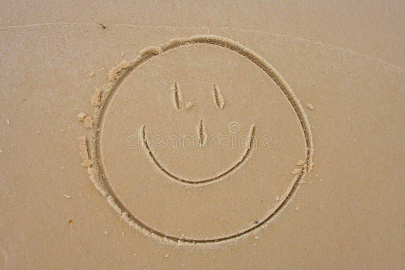Smiley-Gesicht im Sand lizenzfreie stockbilder