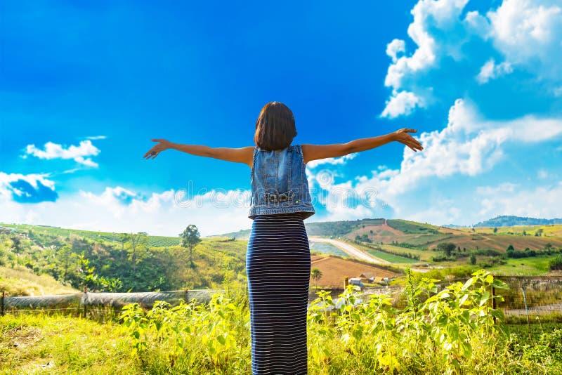 Smiley heureux de jeune femme asiatique et émotion se sentante de fraîcheur bonne avec le fond de ciel bleu photos stock