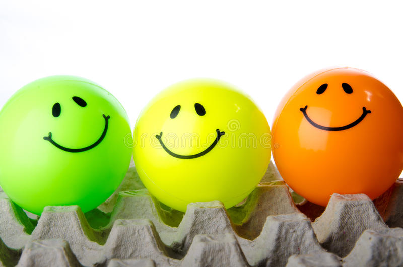 Smiley icon. Painted on a colored ball captured on the egg tray stock image
