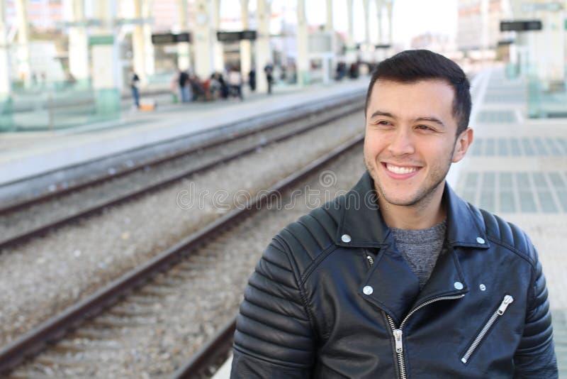 Smiley jong etnisch mannetje die openbaar vervoer met behulp van stock foto