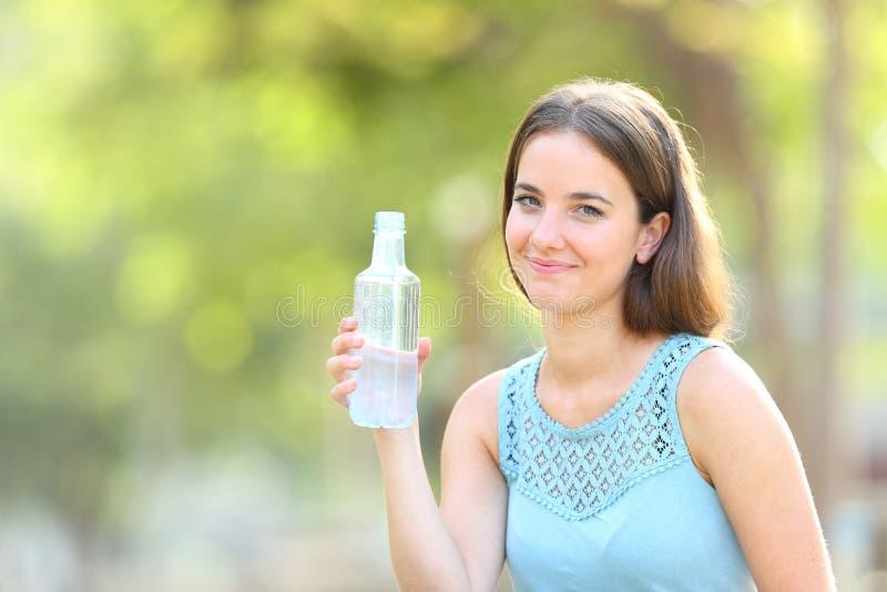 Smiley kobieta trzyma butelkę woda na zielonym tle zdjęcia royalty free