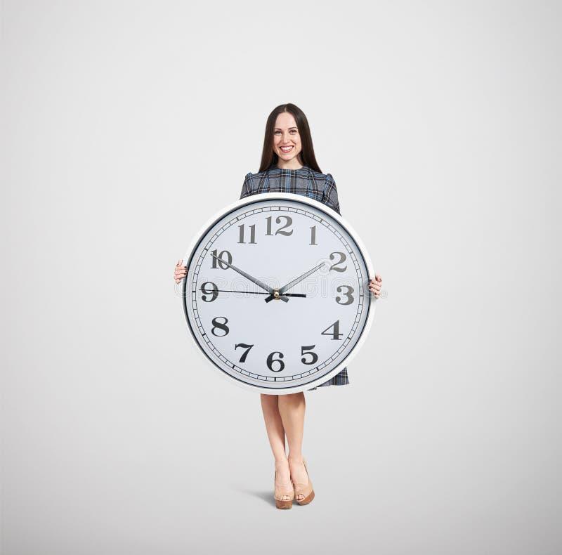 Smiley kobieta trzyma dużego bielu zegar fotografia stock