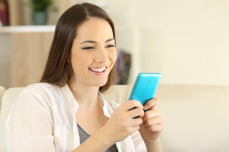 Smiley kvinna som använder den blåa smarta telefonen på en soffa royaltyfri foto