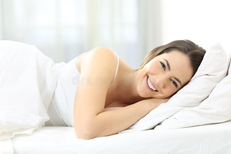 Smiley kvinna som ligger på sängen som ser dig arkivbilder