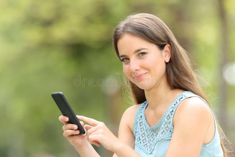 Smiley kvinna som rymmer den smarta telefonen som ser dig på gräsplan royaltyfria foton