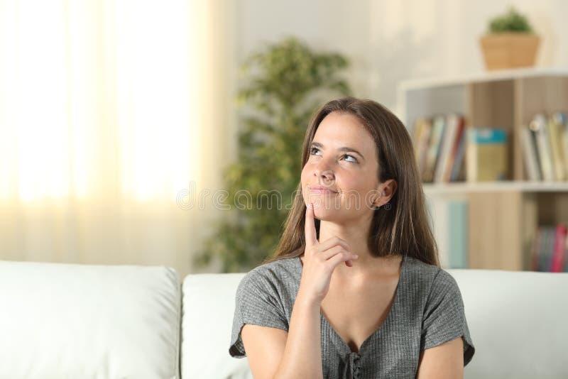 Smiley kvinna som tänker se sidan hemma arkivbilder