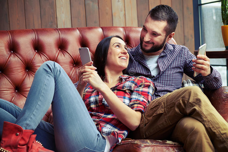 Smiley man and woman resting on sofa stock image