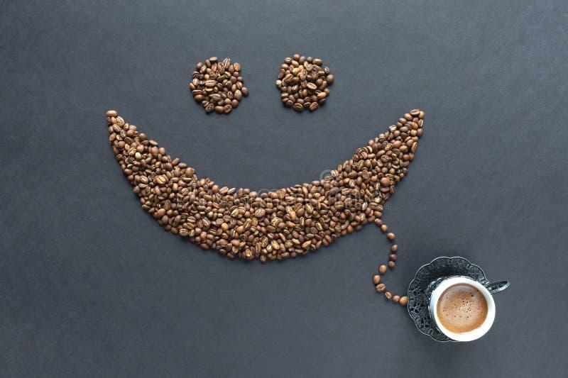 Smiley od kawowych fasoli z filiżanka kawy na czarnym tle zdjęcie royalty free