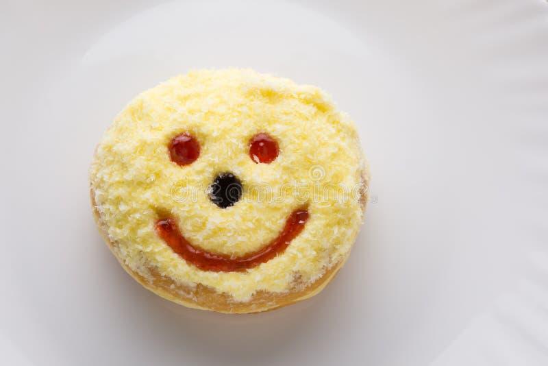 Smiley pączek na bielu talerzu zdjęcia royalty free