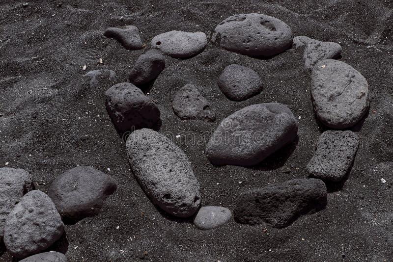 Smiley presentado de piedras en una playa negra en las islas Canarias fotografía de archivo libre de regalías