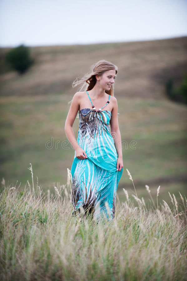 Smiley pretty woman in long dress stock image