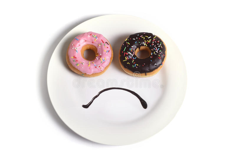 Smiley sad face made on dish with donuts as eyes and chocolate syrup mouth in sugar sweet addiction diet and nutrition stock photo