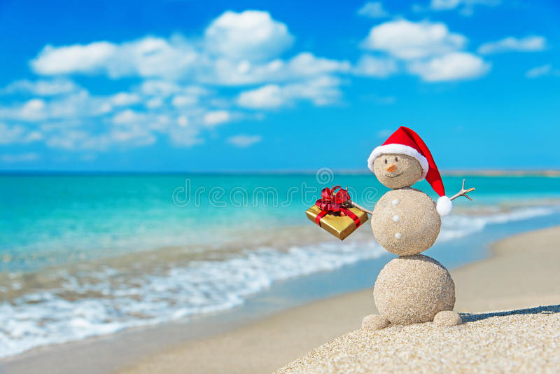 Smiley sandy snowman at beach in christmas hat with golden