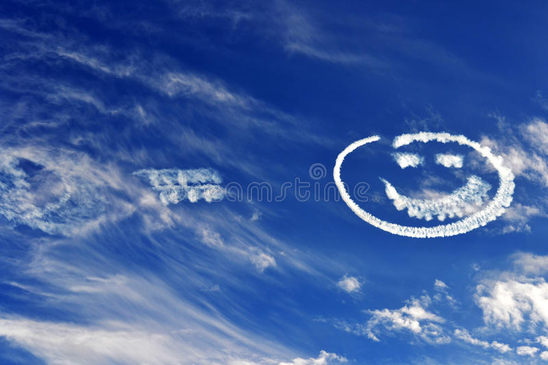 Smiley Skies. A smiley face appears in the blue sky stock photo