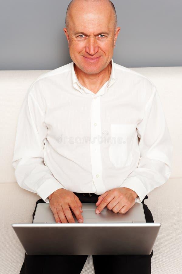 Smiley starszy mężczyzna w biały koszula z laptopem obrazy royalty free