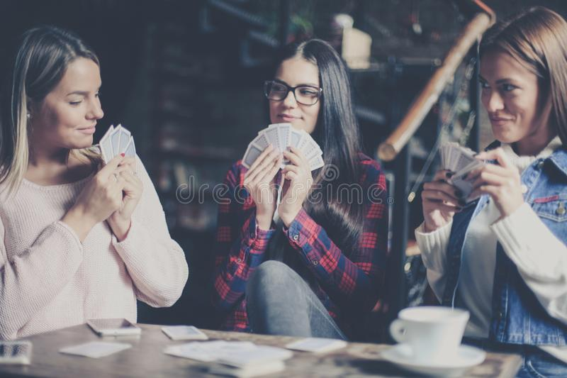 Three best friends in cafe playing together game cards. C royalty free stock image