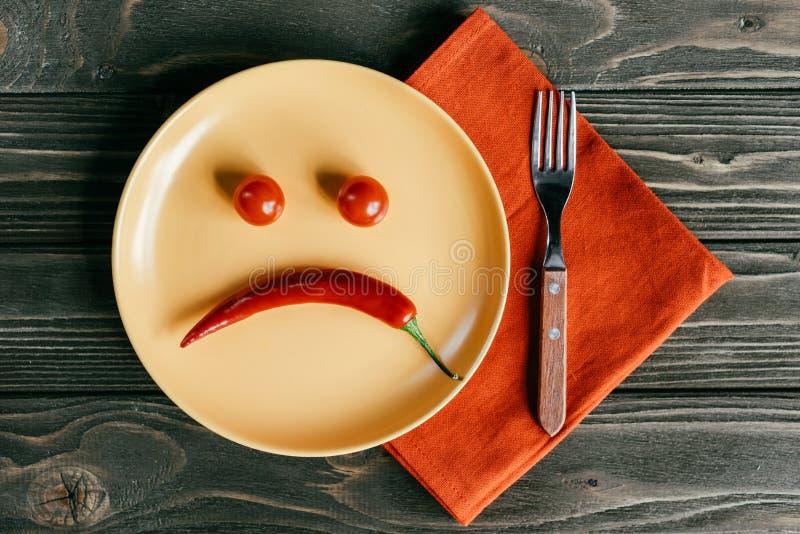 Smiley triste hecho de la pimienta y de los tomates en la placa con la bifurcación fotografía de archivo libre de regalías