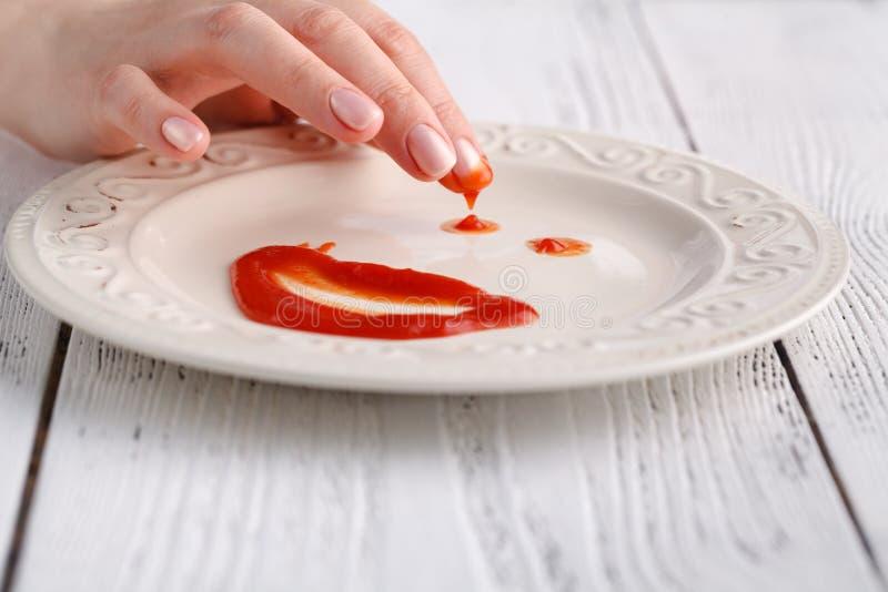 Smiley twarz pomidorowy źródło na bielu talerzu nad drewnianym tłem zdjęcie royalty free