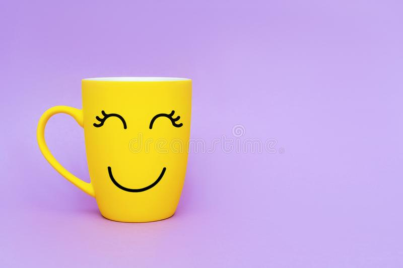 Smiley yellow coffee cup on purple background. Happy friday word concept. Minimalism style, romantic mood, good morning, happiness stock photos