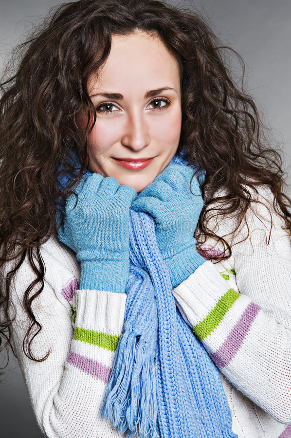 Smiley young woman in blue muffler stock images
