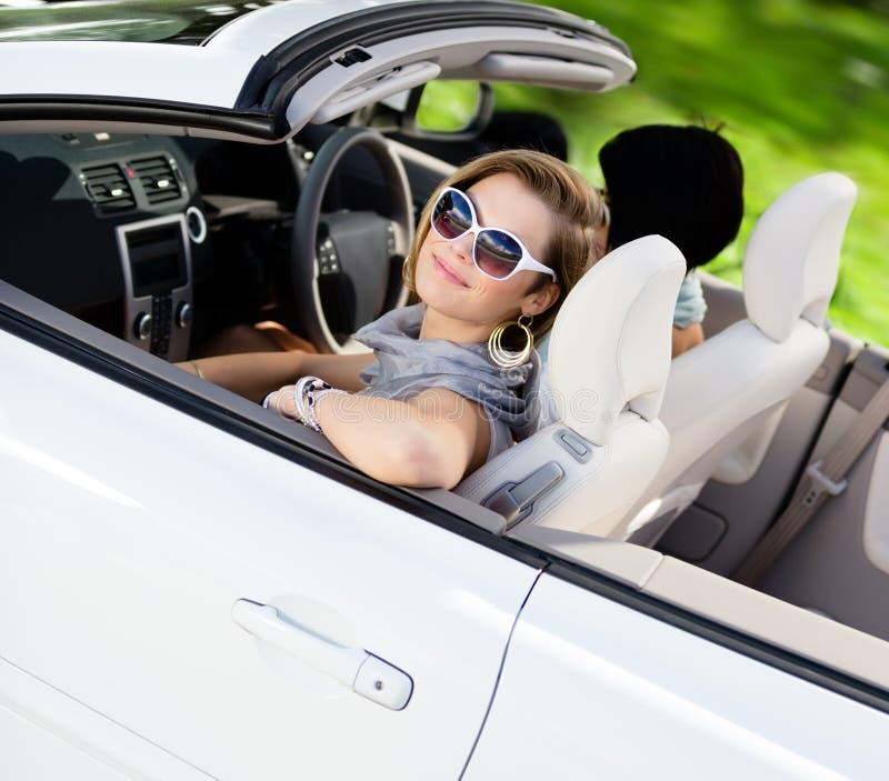Smileyflicka i bilen med hennes vän arkivfoton