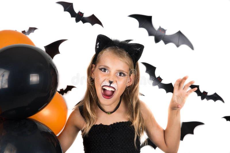 Smileyflickan med dräkten för den svarta katten, halloween makeup och svart och orange ballonger på halloween festar, pumpalappen royaltyfri fotografi