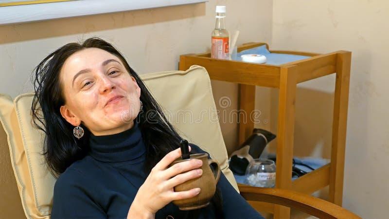 Smileyfrau entspannt sich im Lehnsessel mit Tasse Tee lizenzfreie stockfotografie