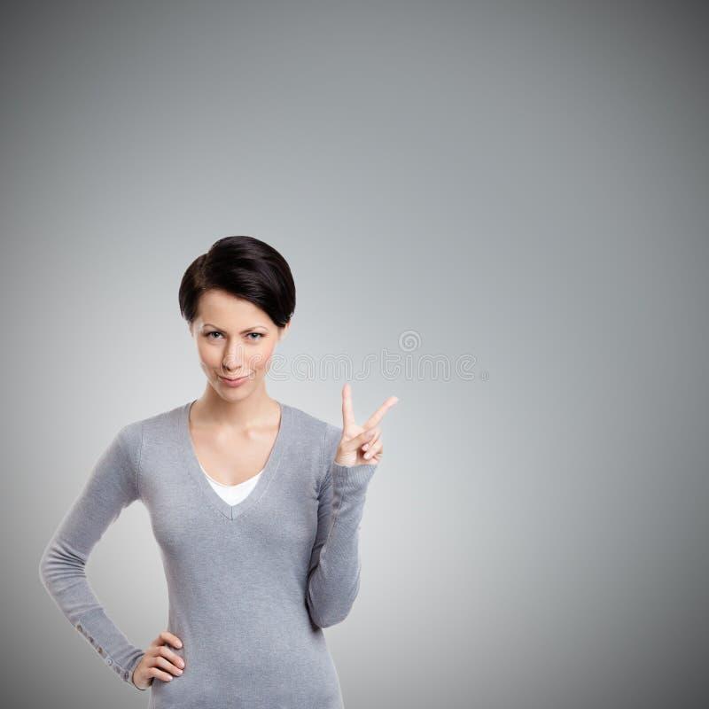 Smileyfrau gestikuliert Friedenszeichen lizenzfreie stockbilder
