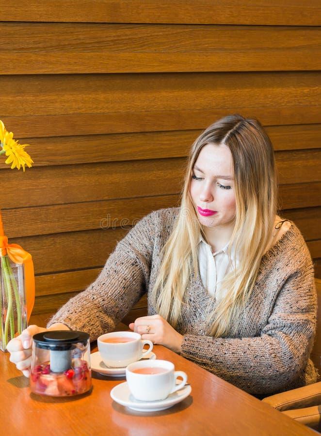 Smileyfrau, welche die Tasse Tee gießt Geschossen im Café lizenzfreie stockbilder