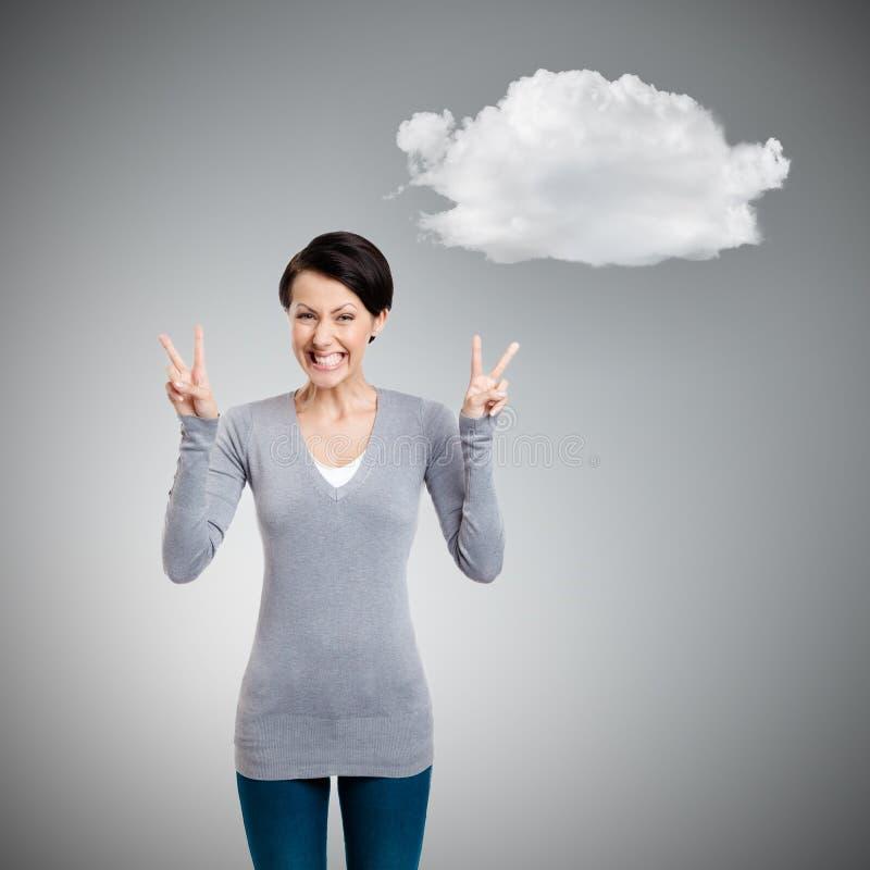 Smileyfrau zeigt Siegzeichen mit zwei Händen stockfoto