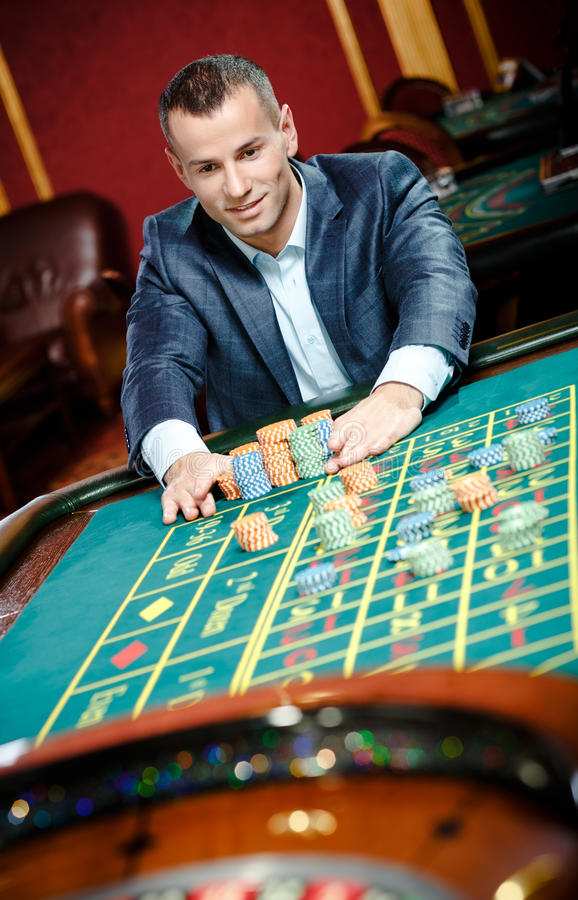 Smileyhasardspelareinsatser som leker rouletten arkivfoto