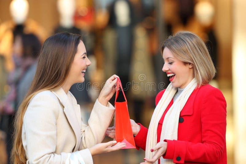 Smileyklant die een gift geven aan een vriend in een wandelgalerij royalty-vrije stock foto