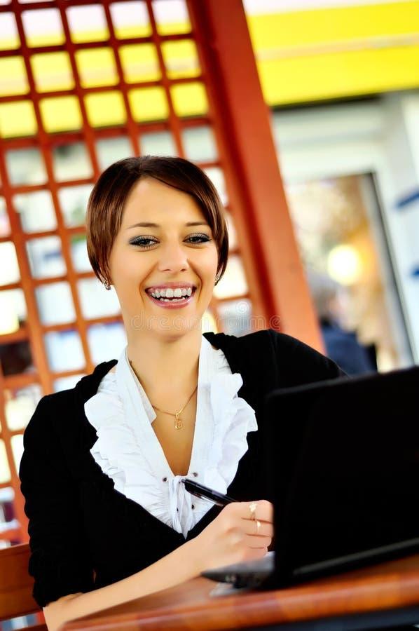 Smileykvinna som använder bärbar dator på cafen arkivfoto