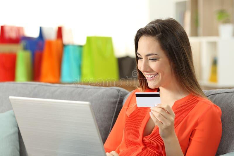 Smileykvinna som betalar på linje med kreditkorten arkivfoton