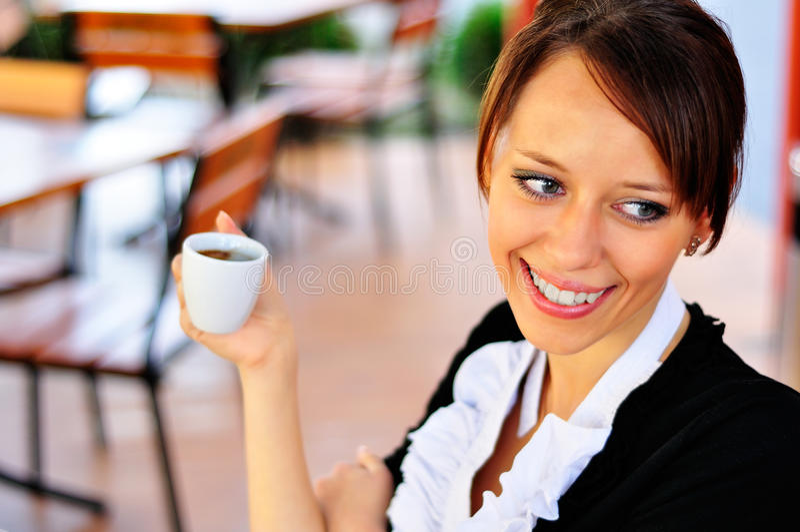 Smileykvinna som rymmer en kopp av kaffe i en hand royaltyfri bild