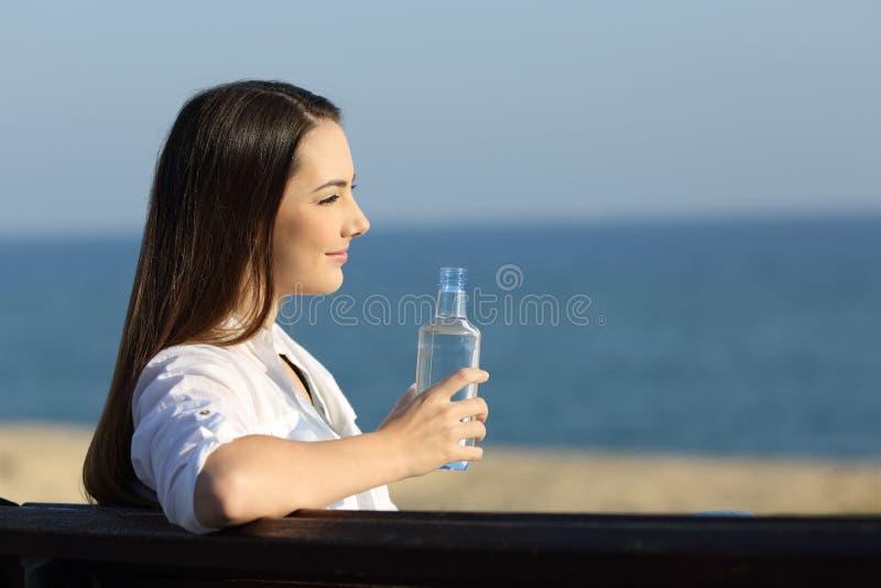 Smileykvinna som rymmer en vattenflaska på stranden fotografering för bildbyråer