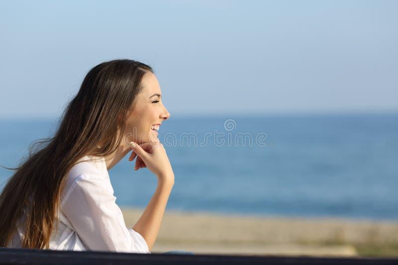 Smileykvinna som ser framåtriktat på stranden royaltyfri fotografi